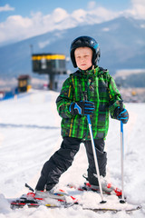Boy in full ski equipment at the mountain ski resort