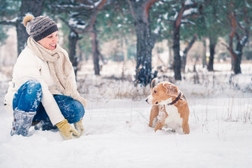 Woman playing with her pet in snow