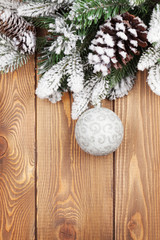 Christmas fir tree with snow and bauble on rustic wooden board