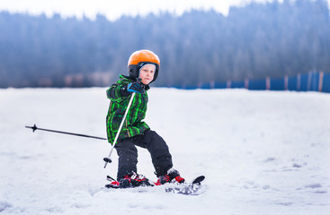 Little boy slides on skis down along the snow slope