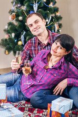 Love couple under christmas tree with wine