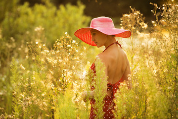 Beautiful woman walks among high wildflowers