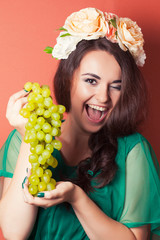 beautiful young woman wearing wreath and holding green grapes ag