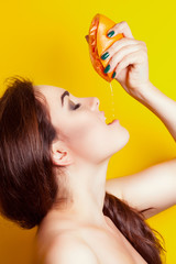 beautiful young woman squeezing juice from grapefruit on her lip