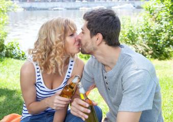 Junges Paar küsst sich auf der Wiese