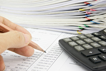 Man is auditing account with pencil and calculator
