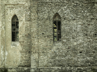 old stone castle wall with broken vertical windows