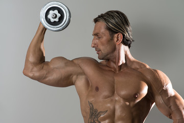 Mature Man Doing Exercise For Biceps On Grey Background