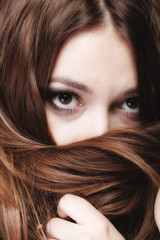 woman covers the face by long brown hairs
