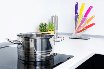 Pot in modern kitchen with induction stove.