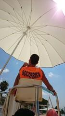 Socorrista bajo sombrilla con rayo de sol