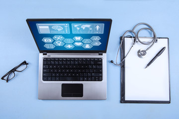 Computer laptop, stethoscope and clipboard