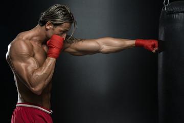 Mature Man Exercising Bag Boxing In Studio