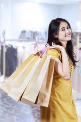 Happy shopaholic holding shopping bags