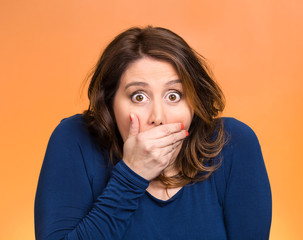 Shocked young woman, covering her mouth stunned