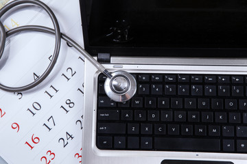 Laptop computer, stethoscope, and calendar