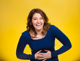 Laughing woman hearing good news, joke on yellow background