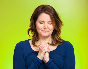 Woman praying, hoping for best, asking forgiveness