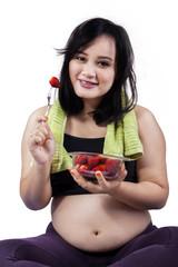 Pretty pregnant woman eats strawberry
