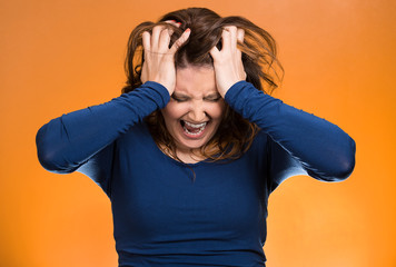 Stressed business woman, pulling her hair out, orange background