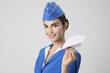 Charming Stewardess Holding Paper Plane In Hand. Gray Background - 69555102