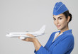 Charming Stewardess Holding Airplane In Hand. - 69555104