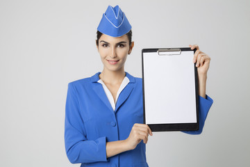 Charming Stewardess Dressed In Blue Uniform with empty blank in