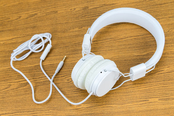 White headphone on wooden background