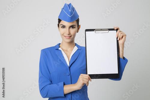 Charming Stewardess Dressed In Blue Uniform with empty blank in - 69555108