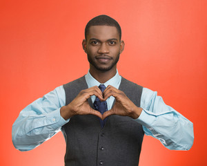Man makes hand heart shape, isolated on red background
