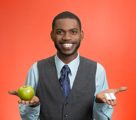 Man holding green apple in one hand, pills, vitamins in another