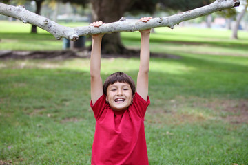 Boy in the park hanging from tree