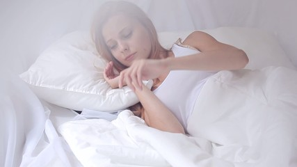 Girl with mobile phone in bed