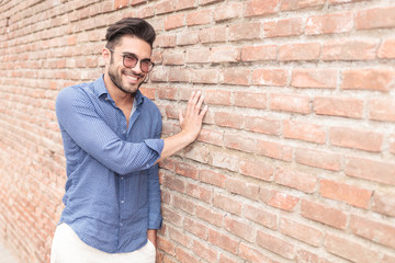 smiling casual man touching brick wall