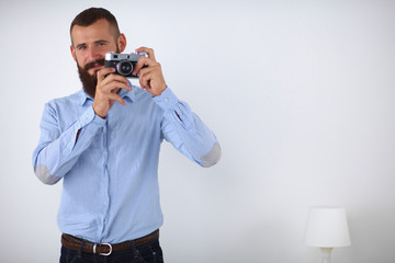Young beard man focusing at you with his camera while standing