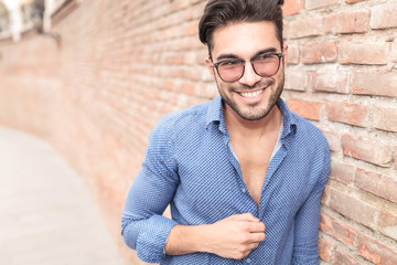 man with glasses looks to  side and laughs