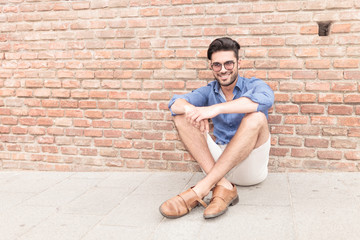 man sitting near brick wall and smiles