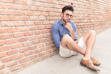 man looking pensive while sitting on the sidewalk