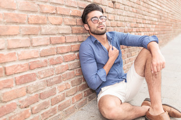 casual man sitting near brick wall looking up