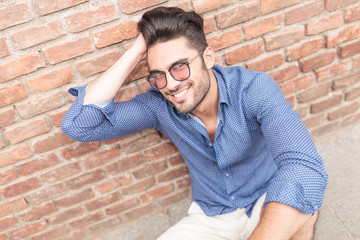 man with glasses fixing his hair while seated