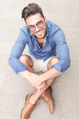 smiling young casual man with glasses sitting on the sidewalk