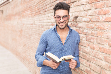 smiling young man holding a book