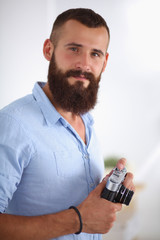 Young beard man holding a camera while standing against white b