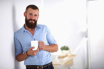 Young man  standing near wall and holding cup of coffee in offi