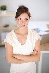 Close-up portrait of a smiling  business woman standing in her