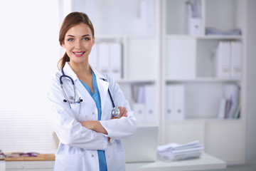 Portrait of young woman doctor with white coat standing in hosp