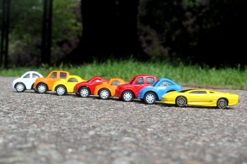 minature colorful cars standing in line on road sale concept