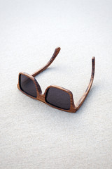 wooden sunglasses lying on the sand