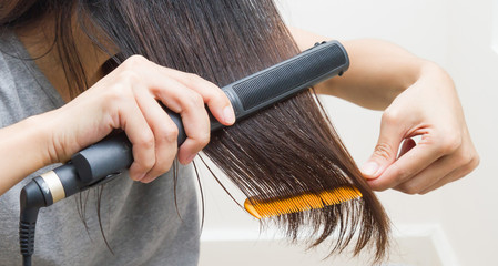 Woman straightening hair with straightener.