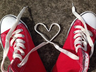 red baseball boots on concrete with heartlaces